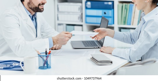 Doctor sitting at office desk and giving a prescription to a female patient, healthcare and medical treatment concept