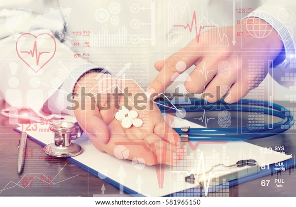 Doctor sitting at table medical chart with stethoscope and holding pills