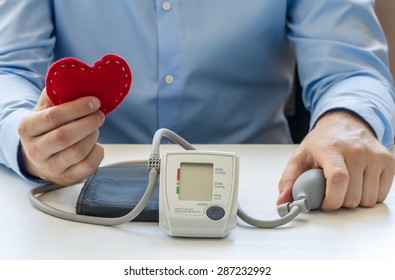 Doctor sitting at the white table and take digital blood pressure monitor and red soft heart in the hands