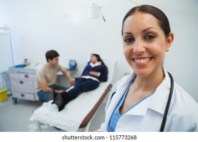 Doctor smiling in hospital room with patient in background