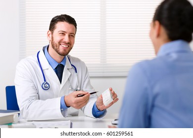 Doctor smiling looking at patient and holding box of medicine in his hand