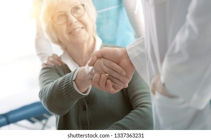 Doctor and smiling senior patient shaking hands in the office before visiting, healthcare and assistance concept