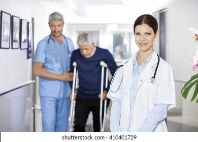 Doctor Smiling While Colleague Assisting Senior Man With Crutche