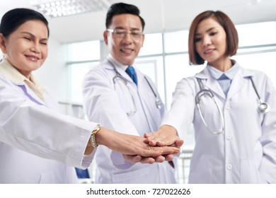 Doctor stacking hands to supports each other before day of work