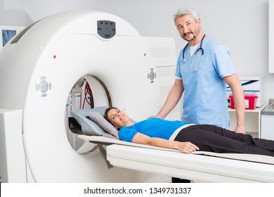 Doctor Standing By Patient Lying On MRI Machine