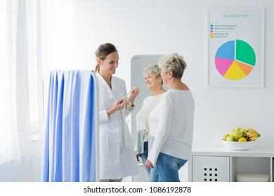 A doctor standing in her office with measuring tape and a patient in front of her. Losing weight concept