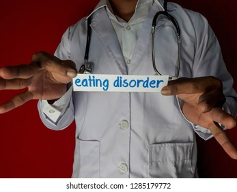 A doctor standing, Hold the eating disorder paper text on red background. Medical and healthcare concept.