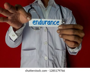 A doctor standing, Hold the endurance paper text on red background. Medical and healthcare concept.