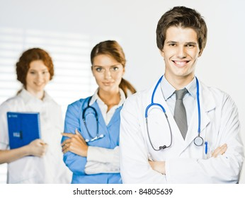 doctor standing on the white background and behind him two nurse