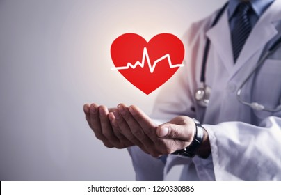 Doctor standing with stethoscope holding red heart with heartbeat.