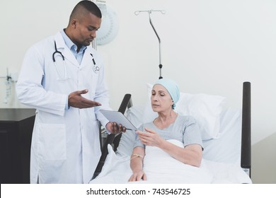 The doctor is standing in the ward next to a woman with cancer. He hands her a tablet on which information about her medical history. They are in a modern clinic.