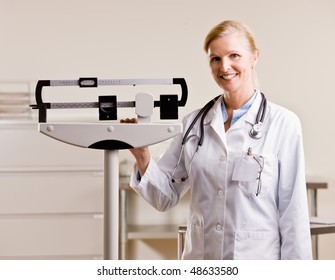 Doctor standing with weighing scales