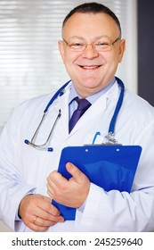 Doctor with stethoscope around his neck looking at the camera.