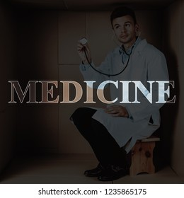 Doctor with Stethoscope in Cardboard Box. Concept of Too Small Clinic. Hospital Ward. Stressful Job, Pressure at Workplace. Lack of Space, Hopelessness. Emotional Burnout of the Physician. Medicine.