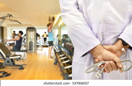 Doctor with stethoscope on fitness room background.