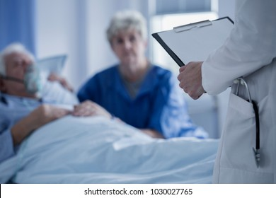 Doctor with stethoscope in the pocket of a white apron holding results of elderly patient