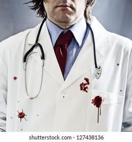 Doctor with stethoscope in white coat with red bloody stains over it and very dramatic side light and harsh shadows.