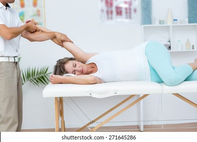 Doctor stretching his patients arm in medical office