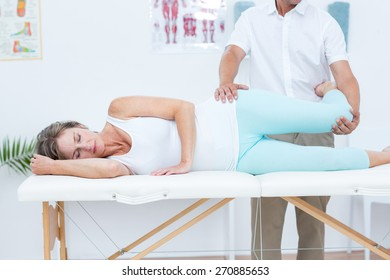 Doctor stretching his patients leg in medical office