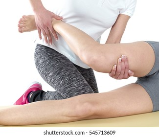 Doctor is stretching woman leg on physiotherapy session.