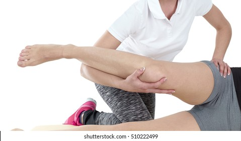 Doctor is stretching woman's leg during a physiotherapy session.