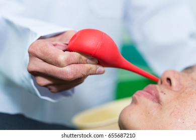Doctor are sucking snot out of his Patient's nose with the Red syringe ball.