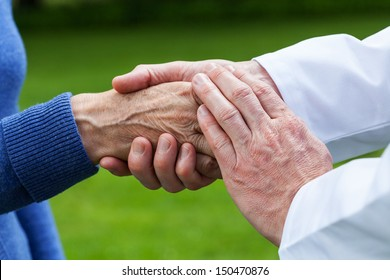 Doctor supporting an elderly woman, green background