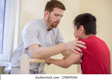 Doctor supports the child during physiotherapy treatment