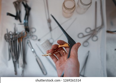 Doctor surgeon holds in his hand a black medical clip for performing an operation against the background of other metal instruments. Neurosurgeon and microsurgery