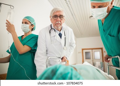 Doctor and surgeon looking at a patient in hospital hallway