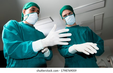 Doctor surgeon and surgical assistant doctor or scrubbing wear surgical gowns and surgical gloves to prepare for surgery before starting the operation, Step by step procedures. Surgery team.