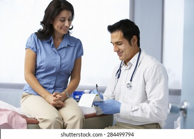 Doctor In Surgery With Female Patient Writing Prescription