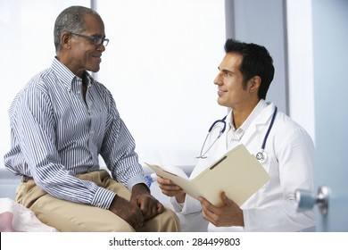 Doctor In Surgery With Male Patient Reading Notes