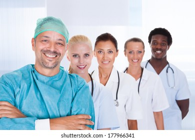Doctor In Surgical Gown With His Coworkers At The Clinic
