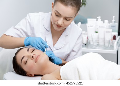 Doctor with syringe with filler for facial contouring or augmentation. Doctor doing beauty procedure for patient. Cosmetological clinic. Healthcare, clinic, cosmetology
