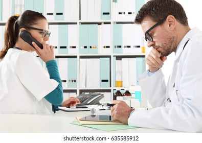 Doctor with the tablet and nurse at phone in medical office