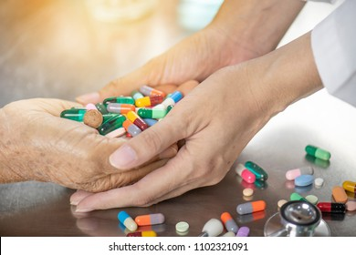 Doctor take care patient by holding hand and dispense many pill in hand.Colorful of vitamin capsules pellet and tablets on metal table close up.Many pills and medicine are supplementary food
