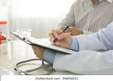 doctor take notes with patient in hospital.  healthcare and medical concept.