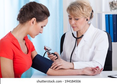 Doctor taking blood pressure of female patient at office