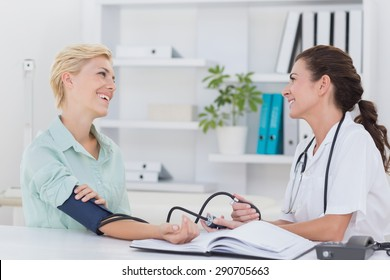 Doctor taking blood pressure of her smiling patient in medical office