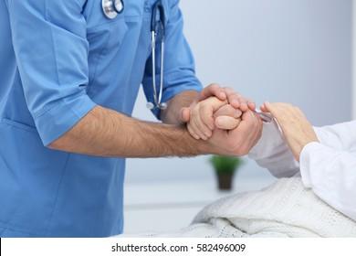 Doctor taking cake of elderly woman in hospital