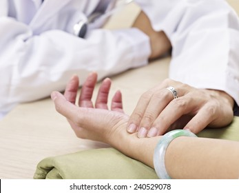 doctor taking a female patient's pulse.