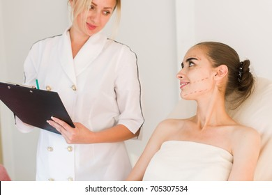 Doctor taking notes while patient is talking in cosmetology clinic. Correction lines on woman face.