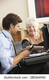 Doctor taking senior woman's blood pressure at home