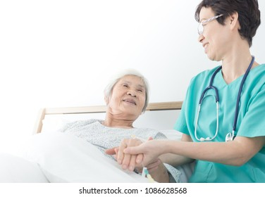 doctor talk with old asian patient about disease symptom , elderly health care,  she holding hand of patient, rehabilitation