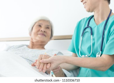 doctor talk with old asian patient about disease symptom , elderly health care,  she holding hand of patient, rehabilitation, happy hospital
