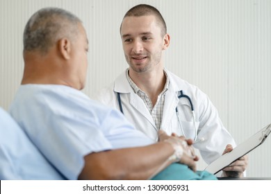 Doctor talking to elderly patient on the bed in hospital.