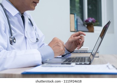 Doctor talking or explaining, having interaction with patient via laptop computer in office. Doctor on videoconference with smart phone on desk. e health, medical online concept. close up