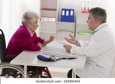 Doctor talking to his disabled senior patient at the office