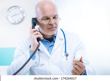 Doctor talking on the phone and looking at medicine's bottle.
